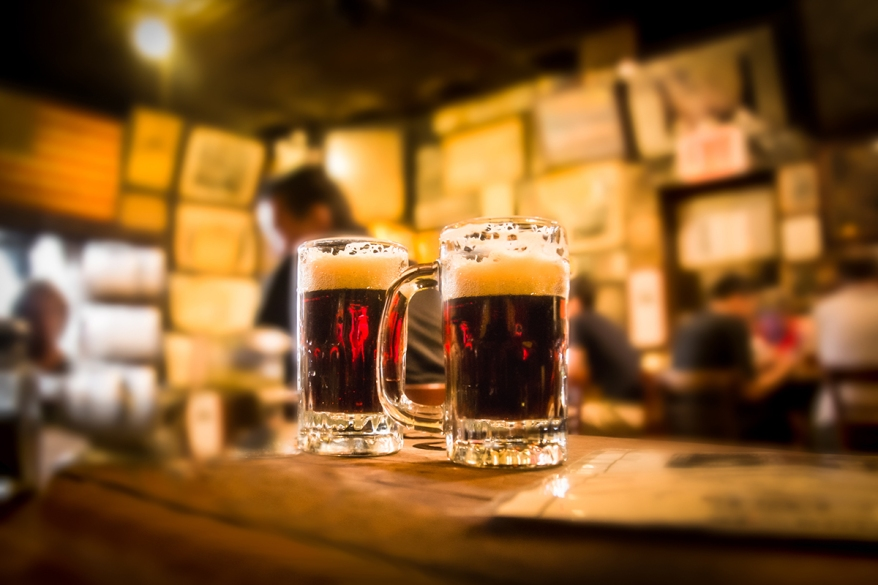 Defocused bar blur with 2 mugs of beer in focus