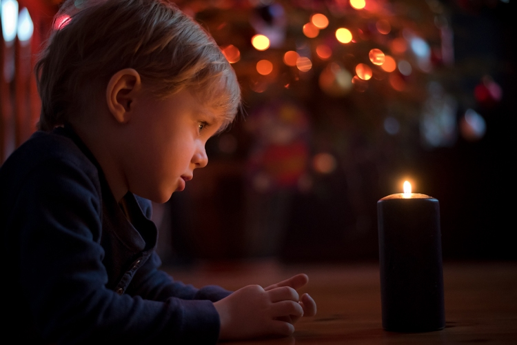 Little toddler boy holding candle with colorful lights from Chri