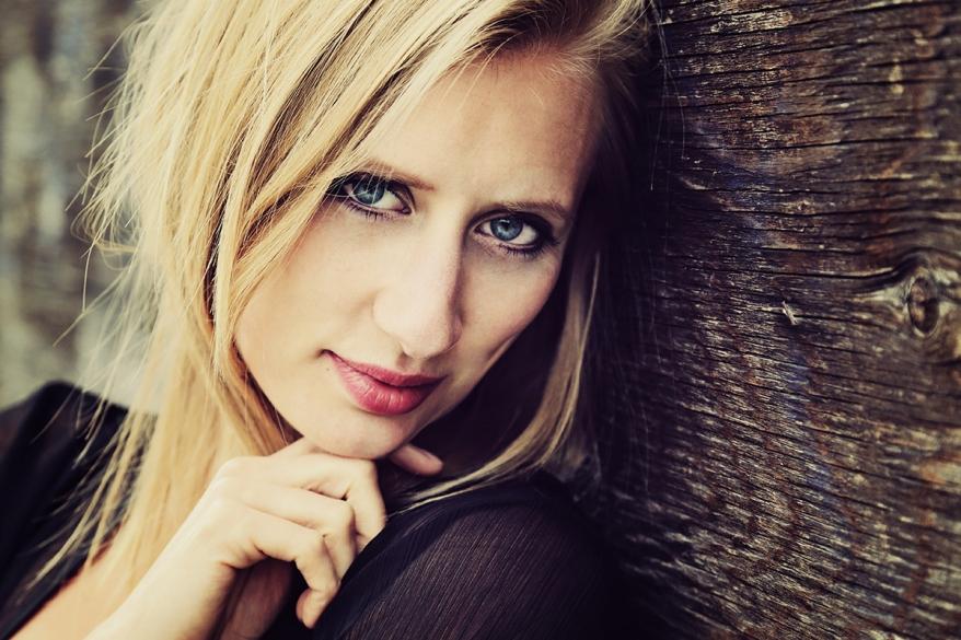 portrait jolie femme blonde souriante contre un mur en bois vint
