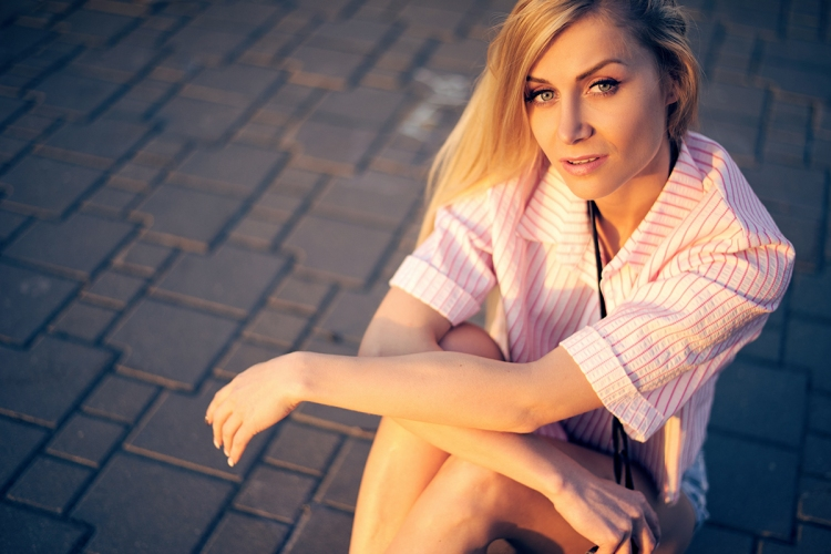 Young beautiful sexy fashionable hipster girl in shorts with cam