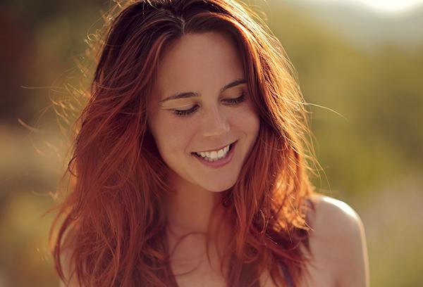 Belle jeune femme heureuse aux cheveux roux et sourire dents bla