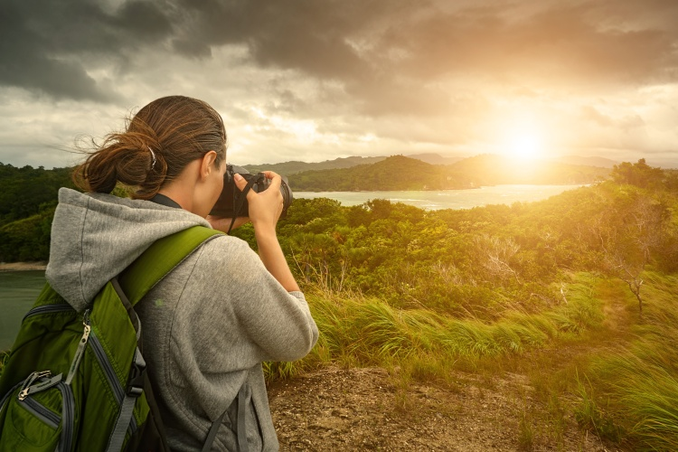 Travelling woman photographer with backpack  making an inspiring