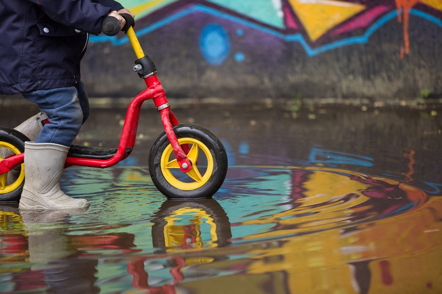 Little child in grey rubber boots cycling after rain.Toddler in
