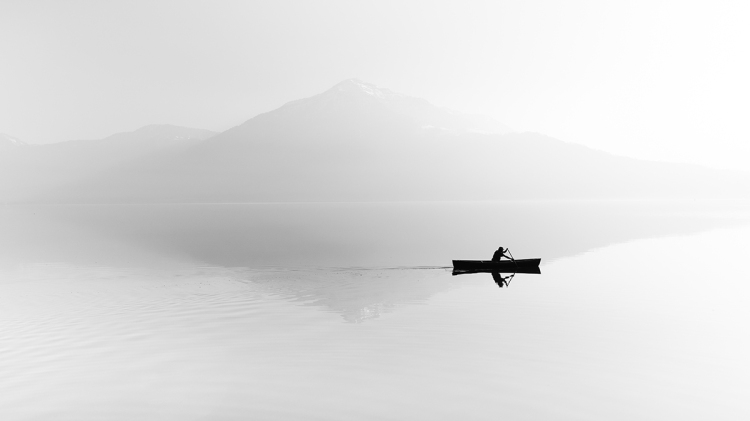 Fog over the lake. Silhouette of mountains in the background. Th