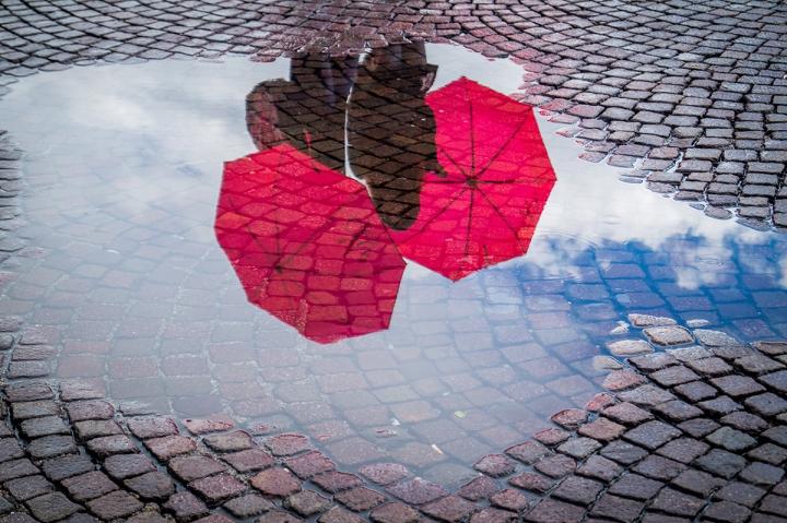 Reflektion von Regenschirmen in einer Pfütze