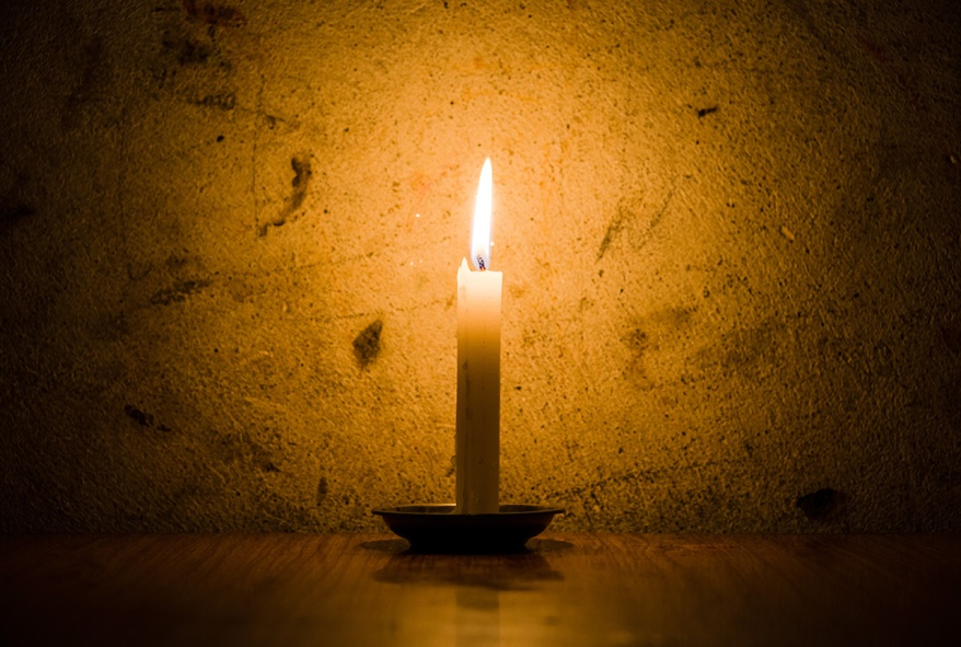 Candle burning, grungy wall background