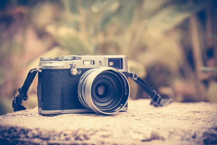 Vintage-style digital camera on boulder over blurred nature back