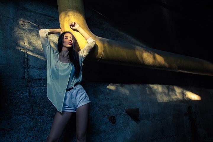 Beautiful alone girl and abandoned sewerage underground with ray