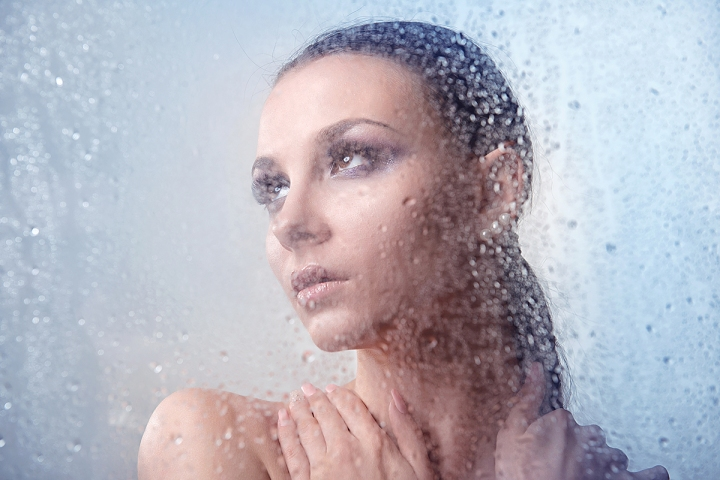 Glamorous brunette woman with makeup smoky eyes with water drops