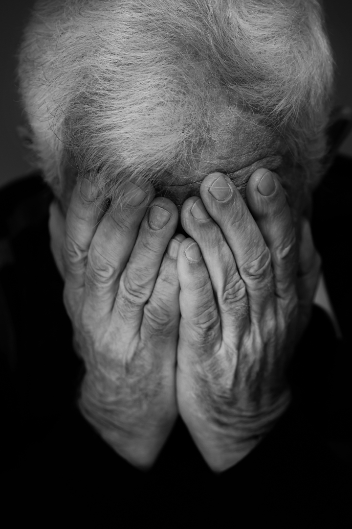 Hands covering face of old man