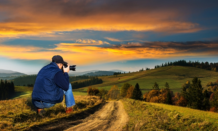 Man photographer in the mountains at sunset