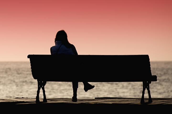 Silhouette of young woman sitting alone on the bench in front of