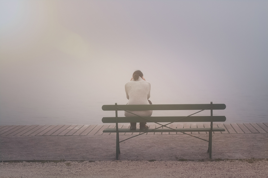 Anonyme junge Frau sitzt betrübt und einsam auf einer Bank im N