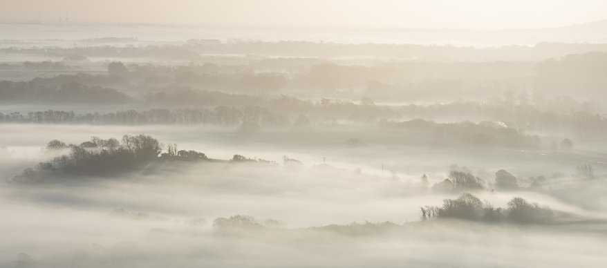 Stunning foggy English rural landscape at sunrise in Winter with