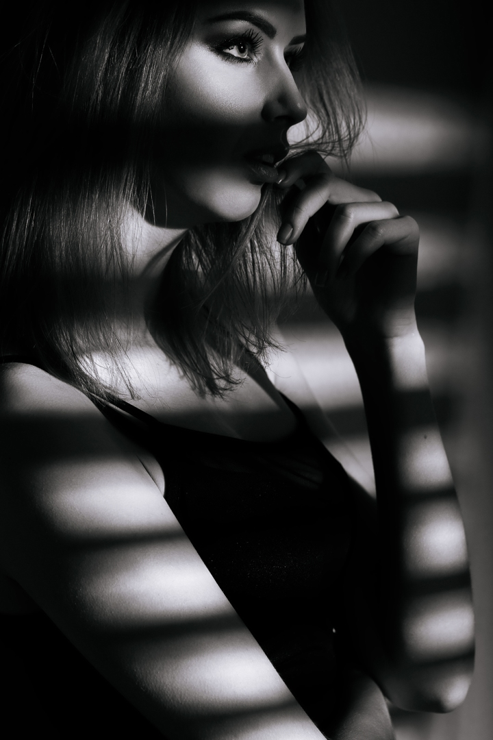 beautiful girl model in black dress with shadow from the blinds