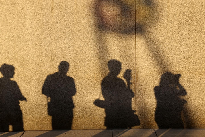 Shadow of photographers against a wall in the evening