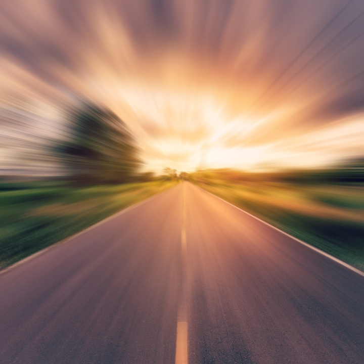 vintage photo of country asphalt road in motion blur at sunset.