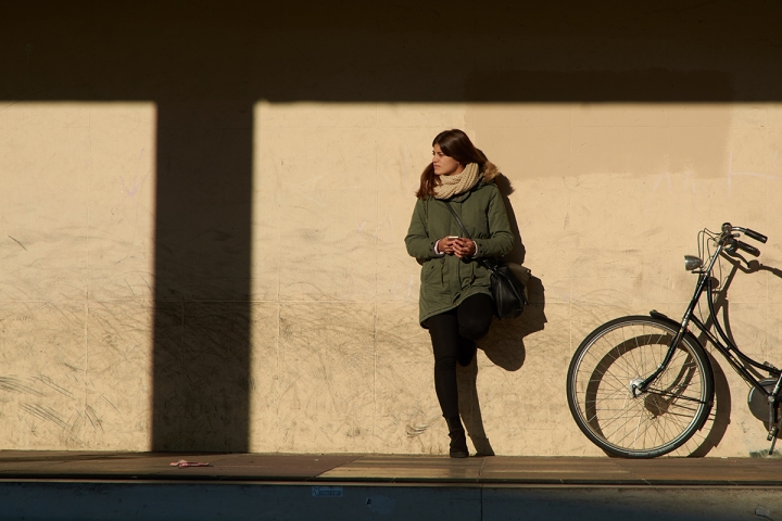 Young millennial using her smartphone and waiting against a wall next to an urban bike
