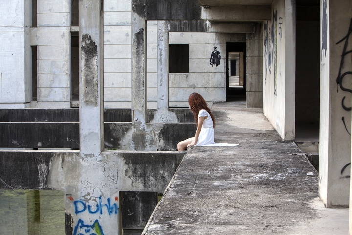 A young woman sitting alone in a desolate place