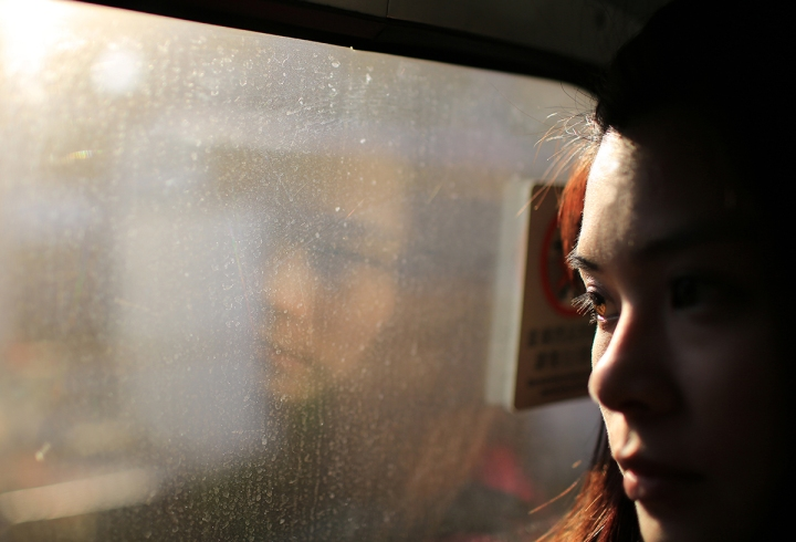 girl face watching out the train with the evening sun bright