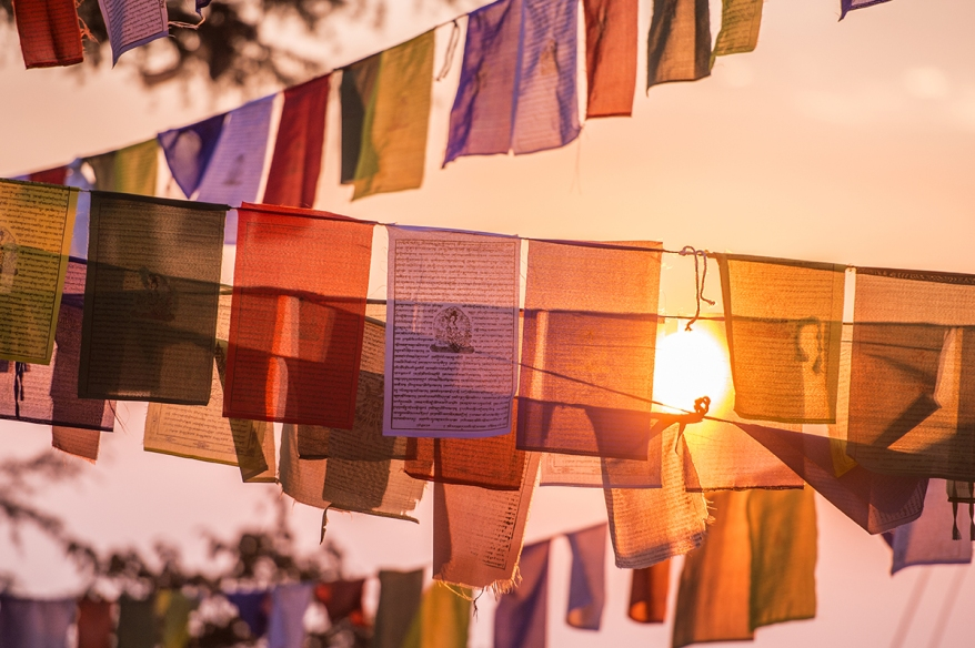 'Selective focus' Vew of some colorful Tibetan flags illuminated by a beautiful sunset in the summit of a Himalayan mountain.