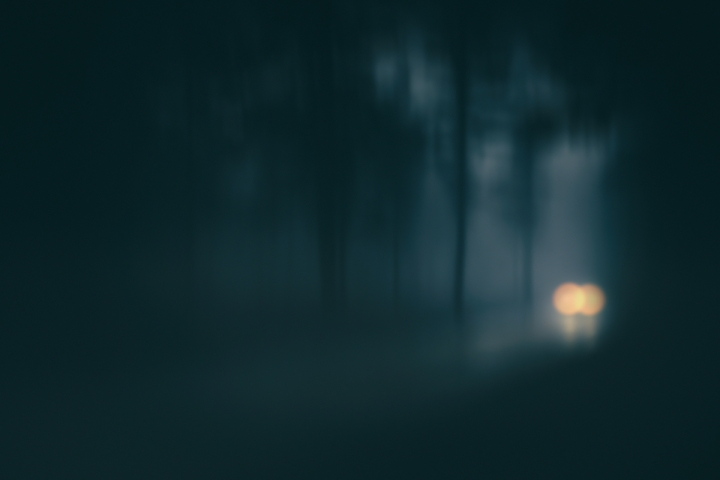 car in country road with fog and low visibility. Blur added