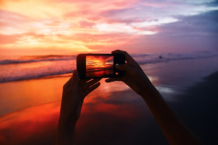 Girl takes a sunset photo on the phone
