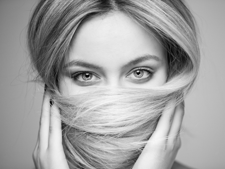 A beautiful woman who covered her mouth with hair, focus on the eyes.