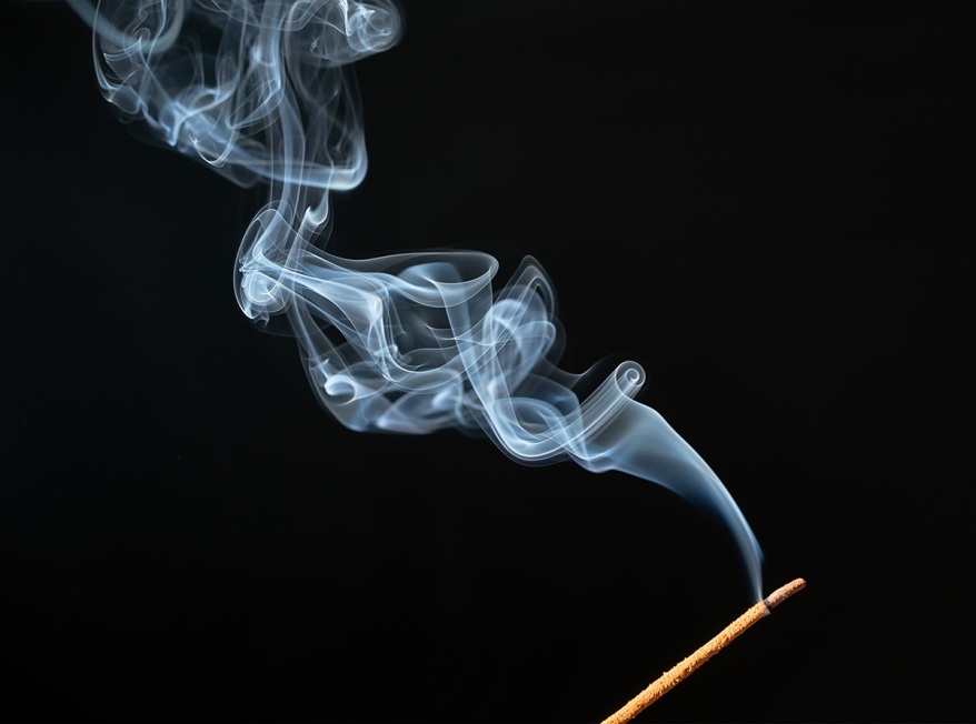 Burning incense stick with smoke on black background.