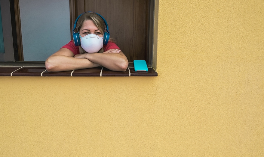 Girl listening music with phone app wearing protective mask at h