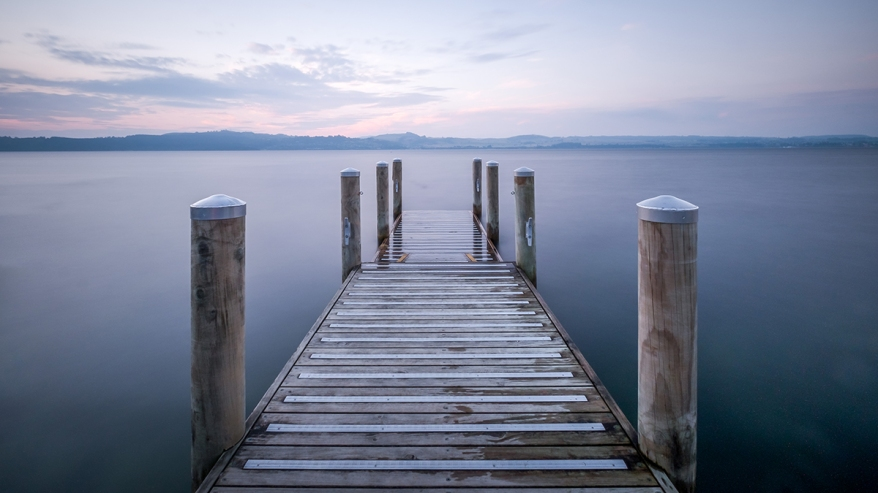 A simple minimalistic photograph of a jetty. The ocean water is