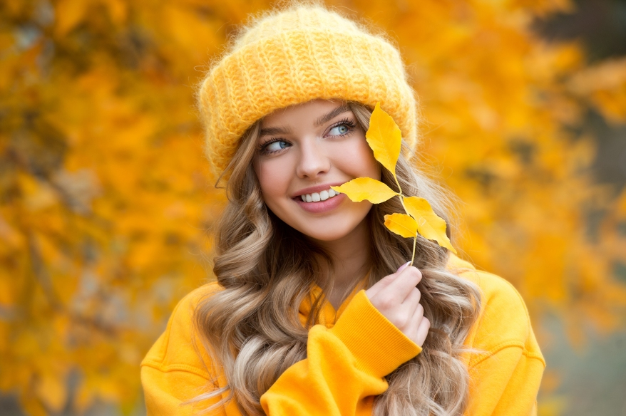 Beautiful girl walking outdoors in autumn. Smiling girl collects