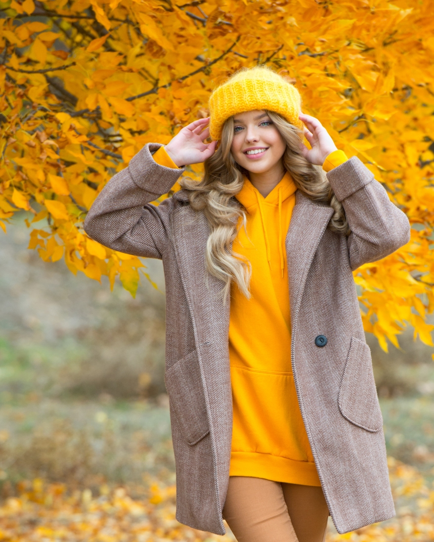 Beautiful woman walking outdoors in autumn. Smiling woman collec