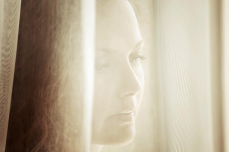 Sad beautiful woman looking through the window